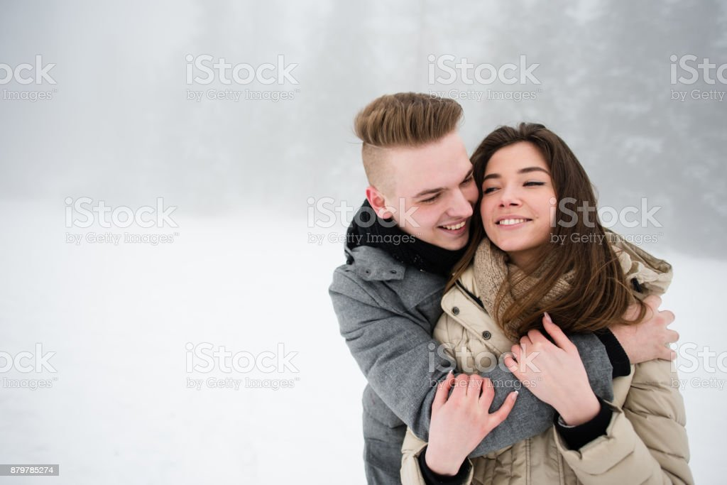 Teen couple in love hugging outdoors stock photo