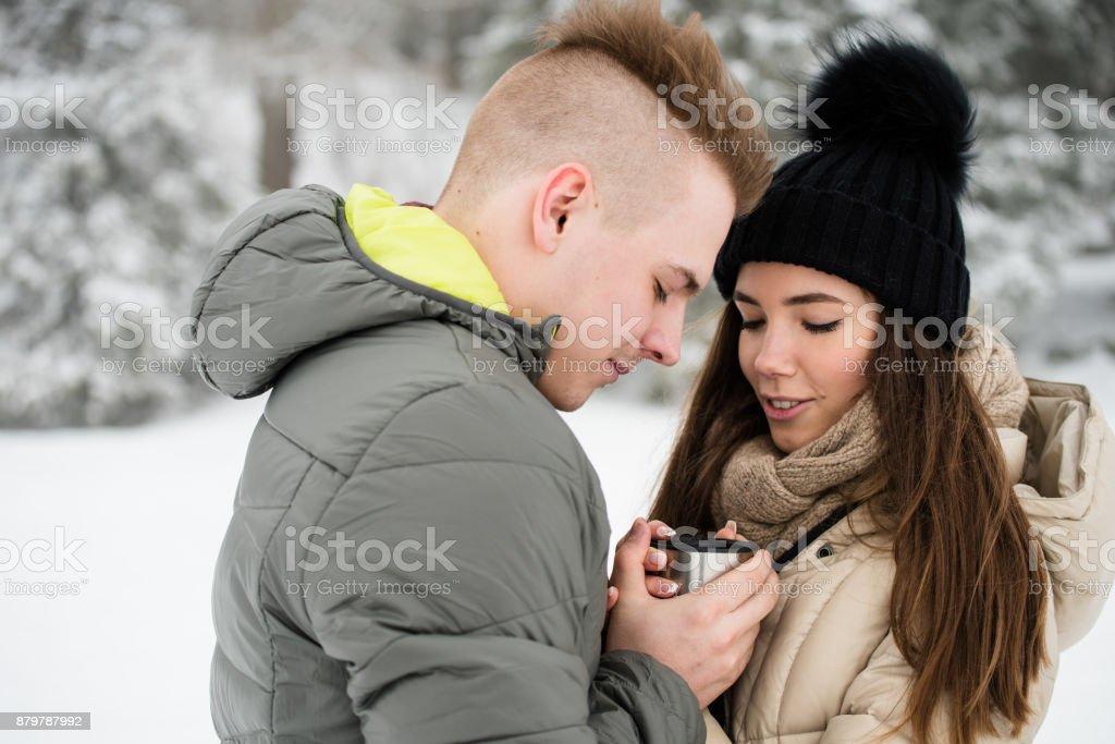Teen couple sharing hot coffee outdoors stock photo