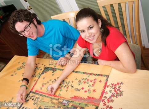 91482522 istock photo Teen couple working on a jigsaw puzzle 182902713
