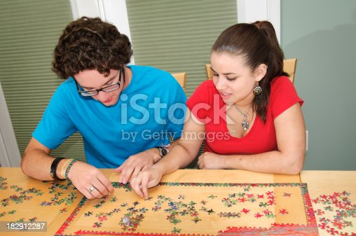 91482522 istock photo Teen couple working on a jigsaw puzzle 182912287