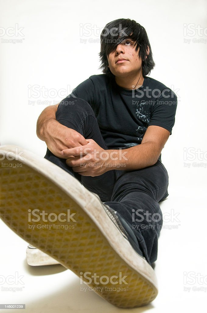 Teen dressed in black sitting on white background forced perspective -  Stock image .