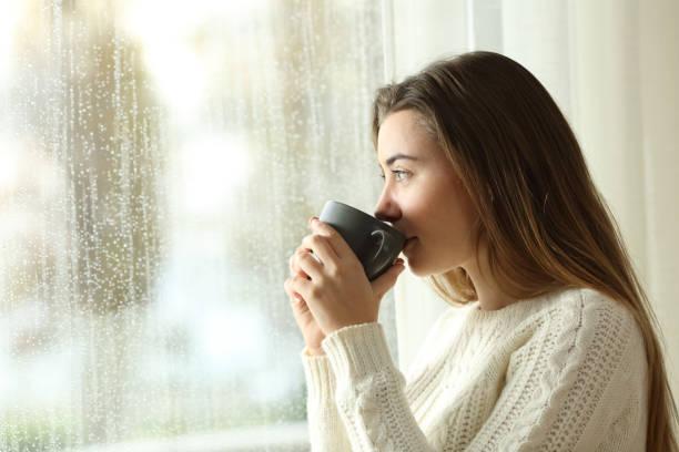 teen bebendo café olhando por uma janela um dia chuvoso - chá bebida quente - fotografias e filmes do acervo