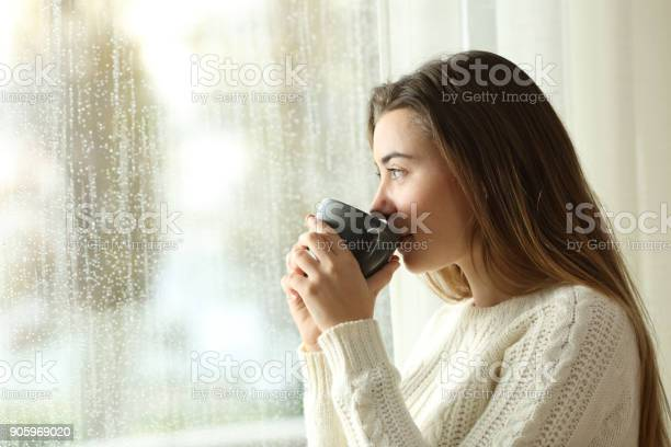 Photo of Teen drinking coffee looking through a window a rainy day