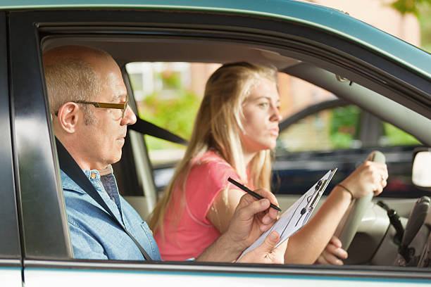 Teen Driver Evaluated by Examiner in Driver Examination_ Subject: A young teenager girl behind the wheel of a car, learning to drive while a driver's training examiner scores performance during a student driving examination. driving instructor stock pictures, royalty-free photos & images