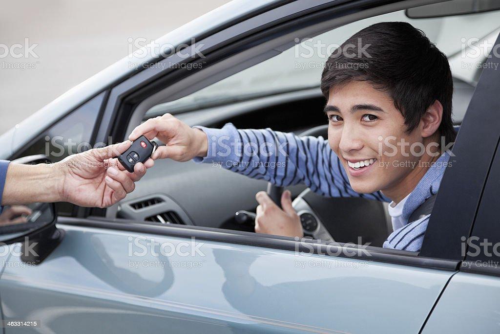 Teen driver getting car keys stock photo
