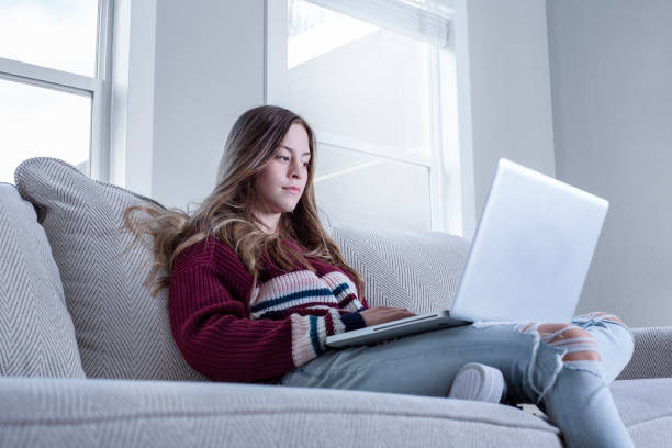 Teen female student studying on the couch doing school work from home stock photo