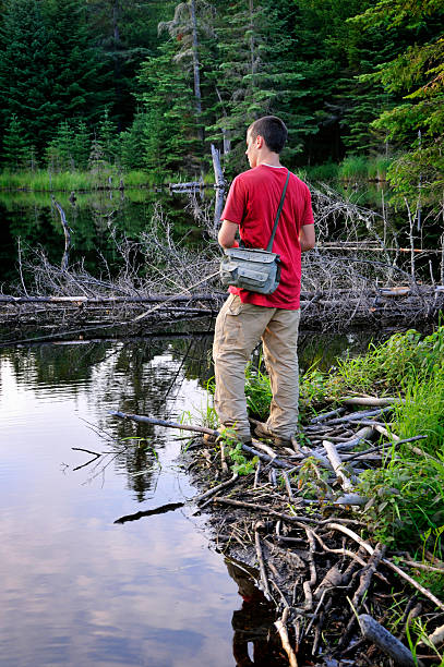 Teen Fisherman Targets Trout in Mountain Beaver Pond stock photo
