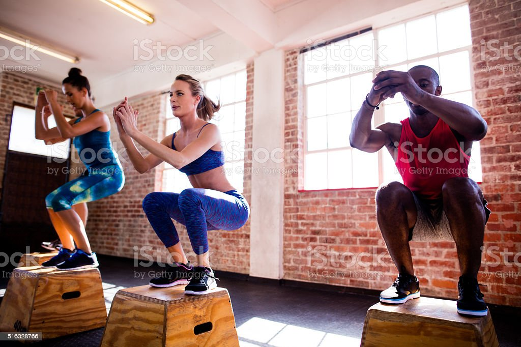 Teen friends jumping in a gym workout stock photo