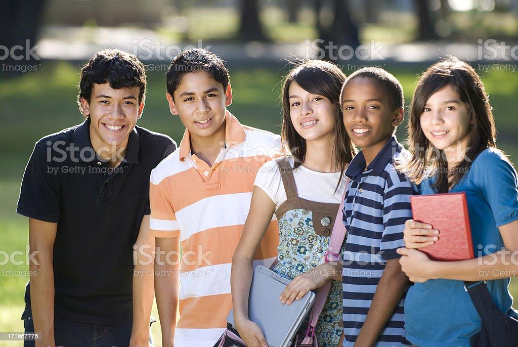 Teen friends preparing to study, facing camera royalty-free stock photo