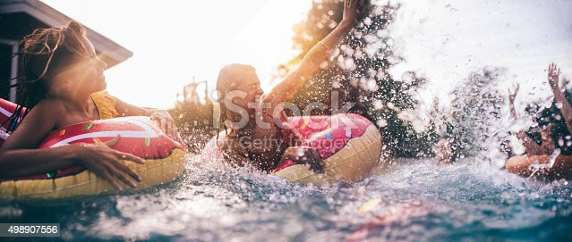 Low angle shot of teenaged friends having fun in a pool in someone's backyard floating on colourful inflatables and playfully splashing each other