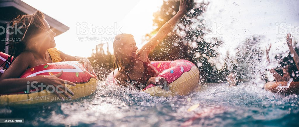 Teen friends splashing in a pool with colourful inflatables stock photo