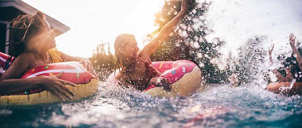 teen freunde mit einem sprung in den pool mit bunten hin - kinderparty spiele stock-fotos und bilder