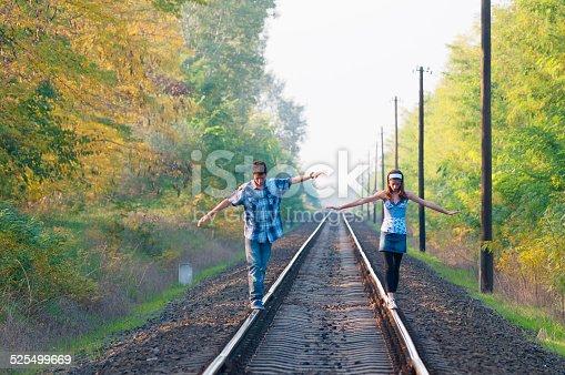 Teen girl and boy balancing on rails at sunset