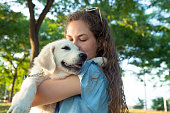 Teen girl holding her puppy labrador golden retriever.