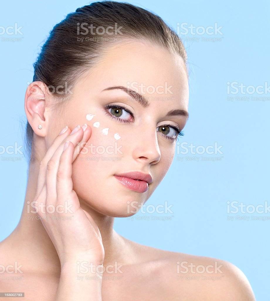 teen girl applying cream on skin around eyes royalty-free stock photo
