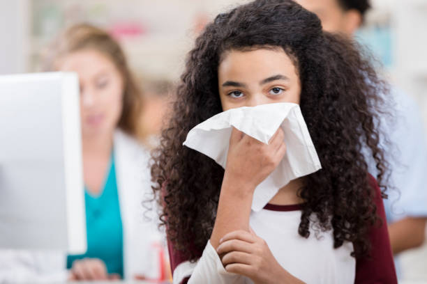 Teen girl appropriately covers her cough to prevent contagion The teen girl appropriately covers her cough to prevent spreading disease.  She is at least six feet away from the people behind her. appropriately stock pictures, royalty-free photos & images
