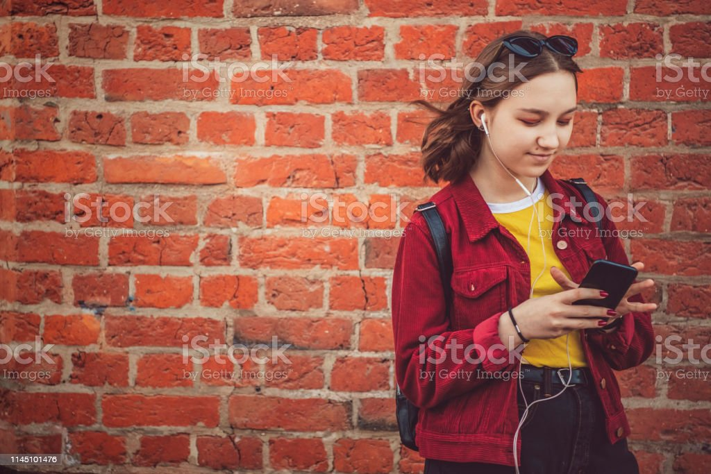 Beautiful young girl standing near a wall with headphones