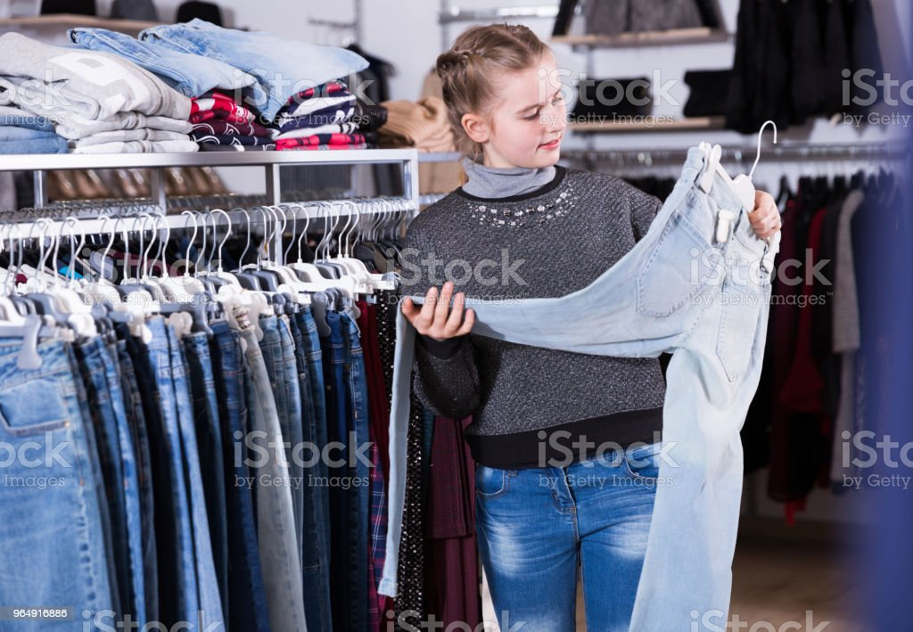 Teen girl choosing jeans in store royalty-free stock photo