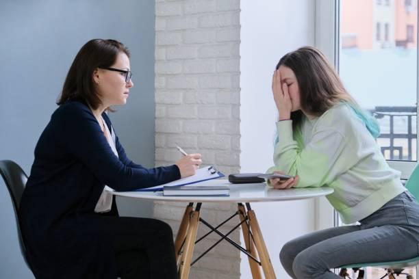 Genç kız psikolog ile toplantıda elleri ile yüzü kapalı stok fotoğrafı