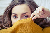 Portrait of beautiful hipster teenage girl in a knitted orange sweater looking at the camera and covering her face with a smile. Lifestyle and people concept. Close up view from above.