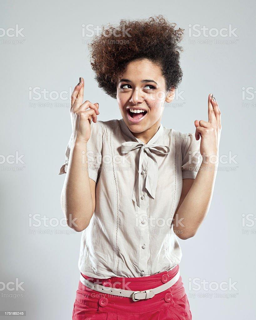 Teen Girl Crossing Fingers Portrait of beautiful teen afro girl crossing her fingers. Studio shot, grey background. 18-19 Years Stock Photo