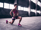 Fit teen girl wearing pink sportswear in a grey gym space warming up for exercise by performing a lunge