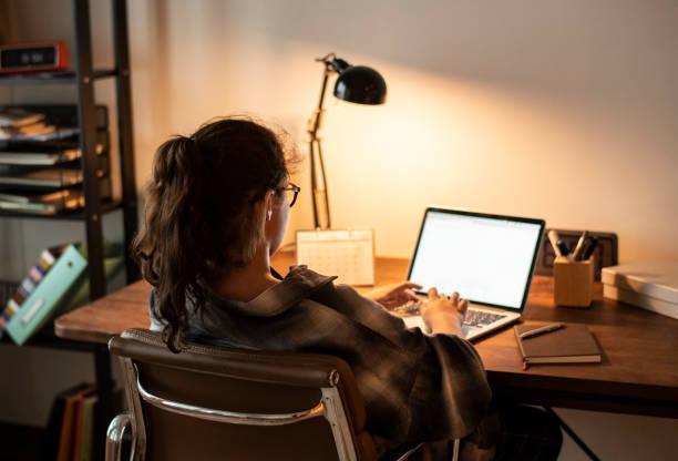 Teen girl doing homework on her laptop stock photo