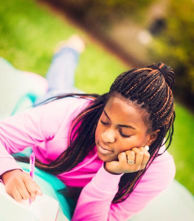 istock Teen Girl Doing Homework Outdoors 186758775