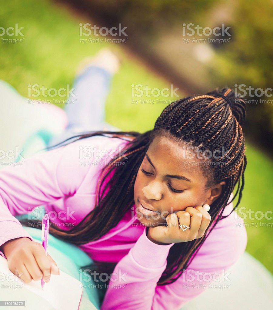 Teen Girl Doing Homework Outdoors stock photo