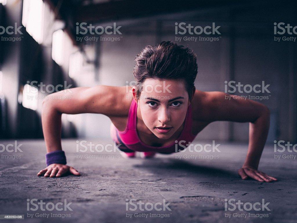 Teen girl doing push ups on a concrete floor stock photo