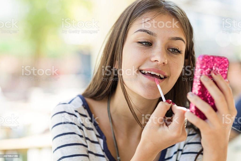 Teen girl fixing her make up stock photo