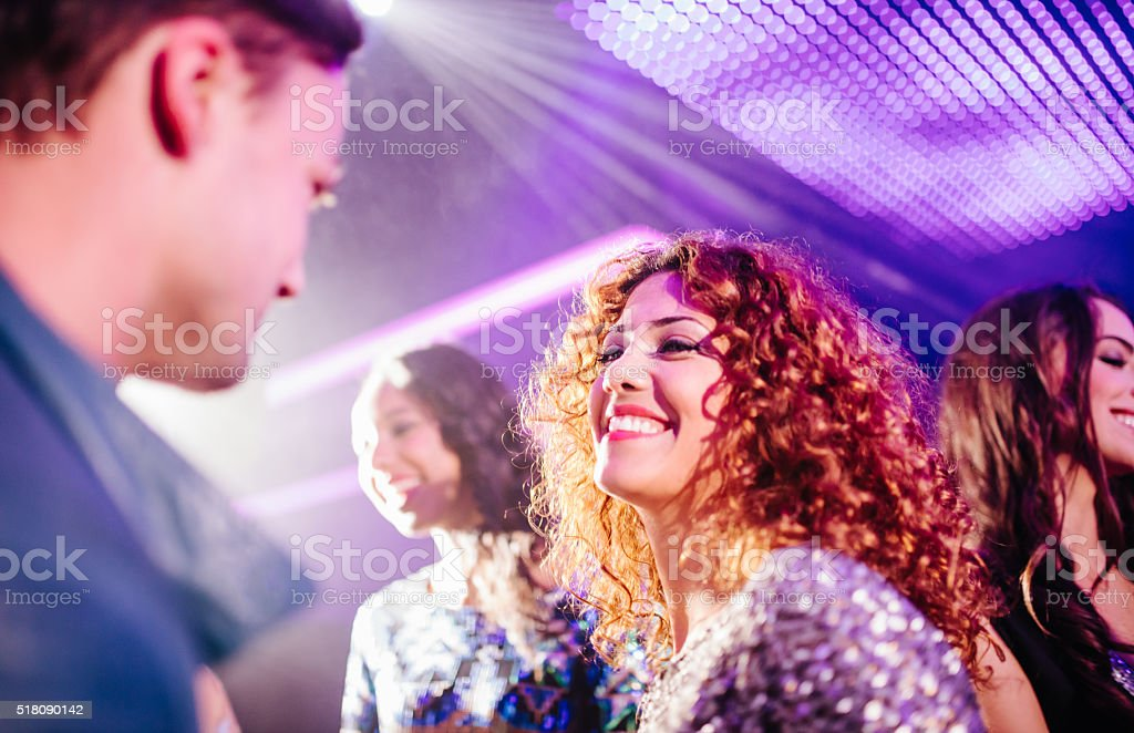 Teen girl flirting with a guy in a night club - Stock image .