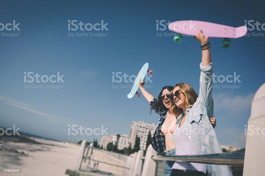 Teen girl friends at the beach lifting their skateboards up stok fotoğrafı
