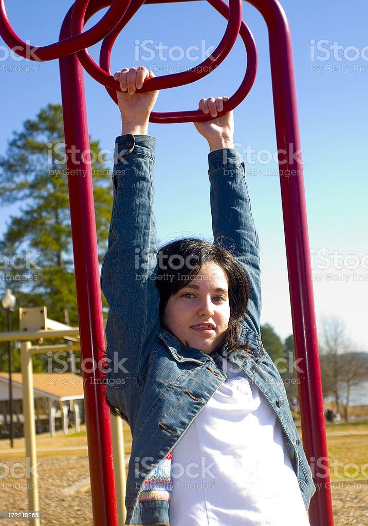 Teen Girl Hangs from Monkey Bars royalty-free stock photo