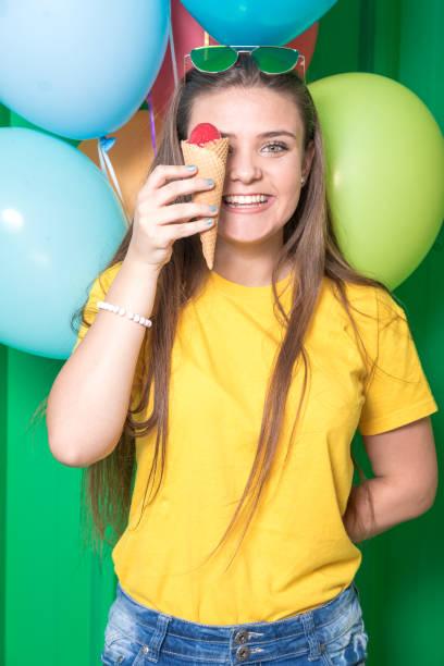 teengirl eistüte über ihr auge zu halten. bunte luftballons in den hintergrund. essen und mode konzept. - eis ballons stock-fotos und bilder