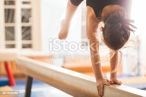 Girl gymnast trains in the gym