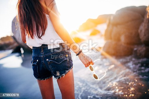 Cropped rearview shot of a teen girl wearing denim shorts and holding her sunglasses at the beach at sundown with sun flare