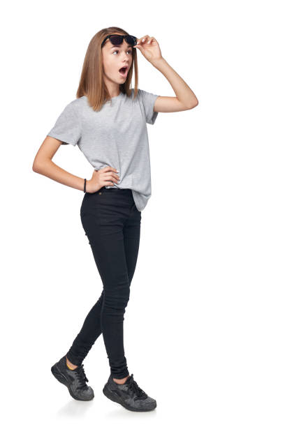 Teen girl in full length standing in sunglasses Surprised teen girl in full length looking with opened mouth away at blank copy space raising her sunglasses in astonishment, isolated on white background skinny pants stock pictures, royalty-free photos & images