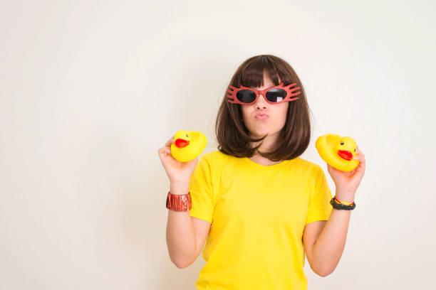 Teen Mädchen in lustigen Gläsern mit Entengesicht und zwei gelben Gummienten, die Spaß haben. Partyrequisiten, Fotostand und Menschenkonzept. – Foto