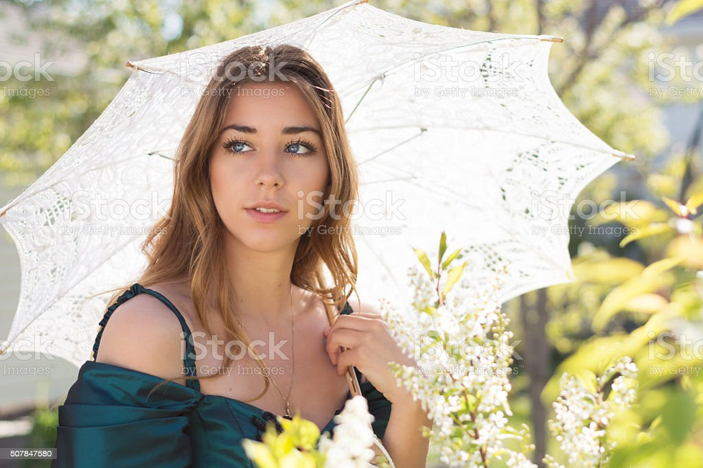 Teen girl in green ball gown with lace parasol, outside. stock photo