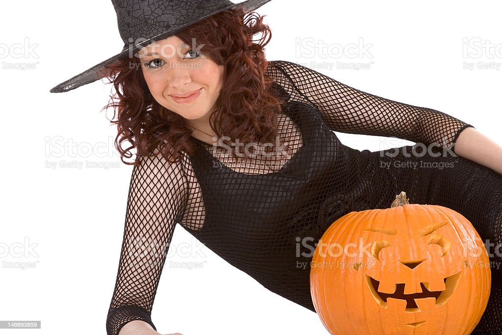 Teen girl in Halloween hat with carved pumpkin stock photo