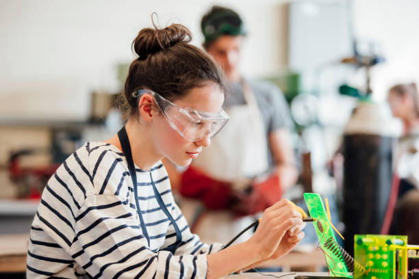 Teen Girl in STEM Class Teenage girl concentrating during STEM lesson. stem topic stock pictures, royalty-free photos & images