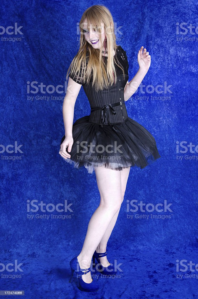 Teen girl in tutu dancing on blue. royalty-free stock photo