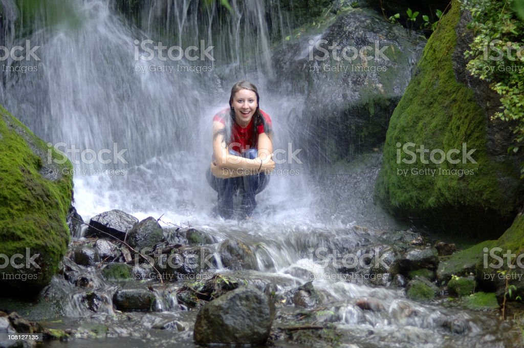 teen girl in waterfall stock photo