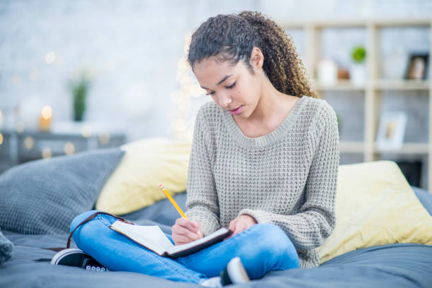 teen girl journaling on her bed - diario foto e immagini stock