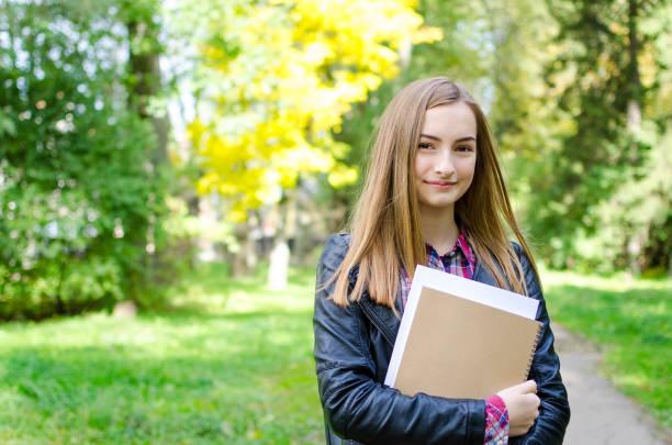 teen girl outdoor holding books - scolara foto e immagini stock