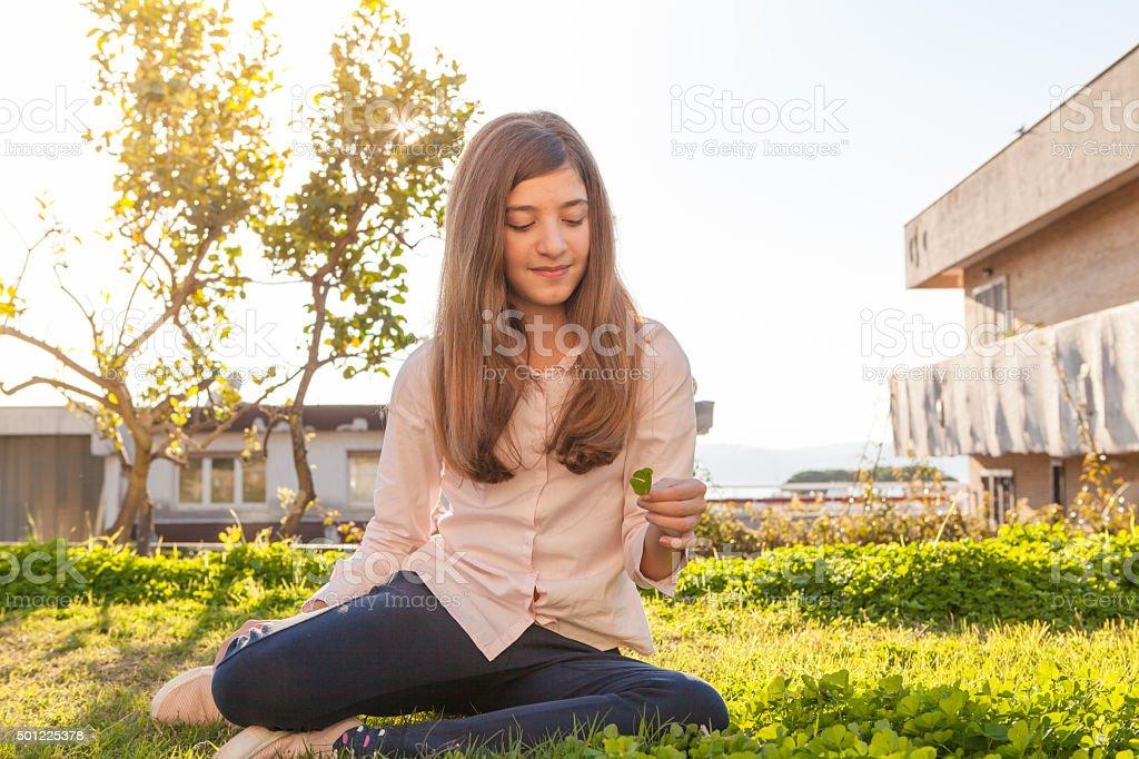 Teen Girl Picking 4-leaf clovers. stock photo