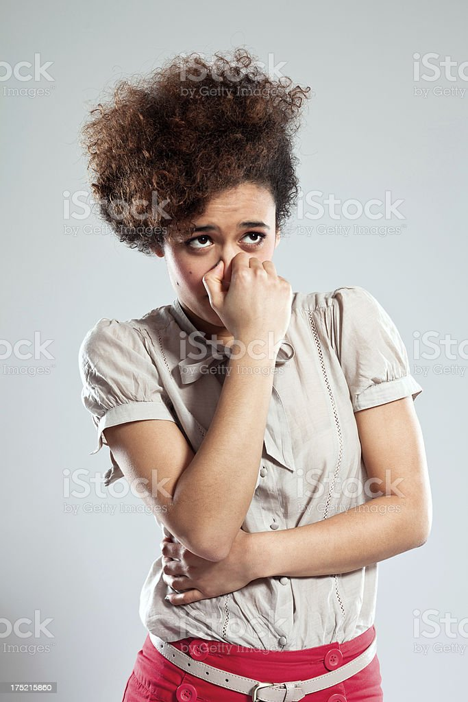 Teen girl pinches nose Portrait of disgusted young woman pinches her nose and looking away. Studio shot, grey background. 18-19 Years Stock Photo