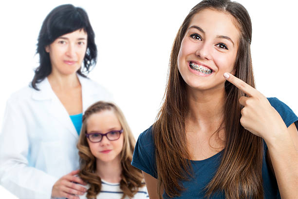 teen girl pointing at dental barces with doctor in background. - brace stock pictures, royalty-free photos & images
