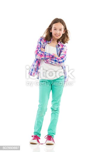 Young girl in lumberjack shirt and green trousers posing. Full length studio shot isolated on white.